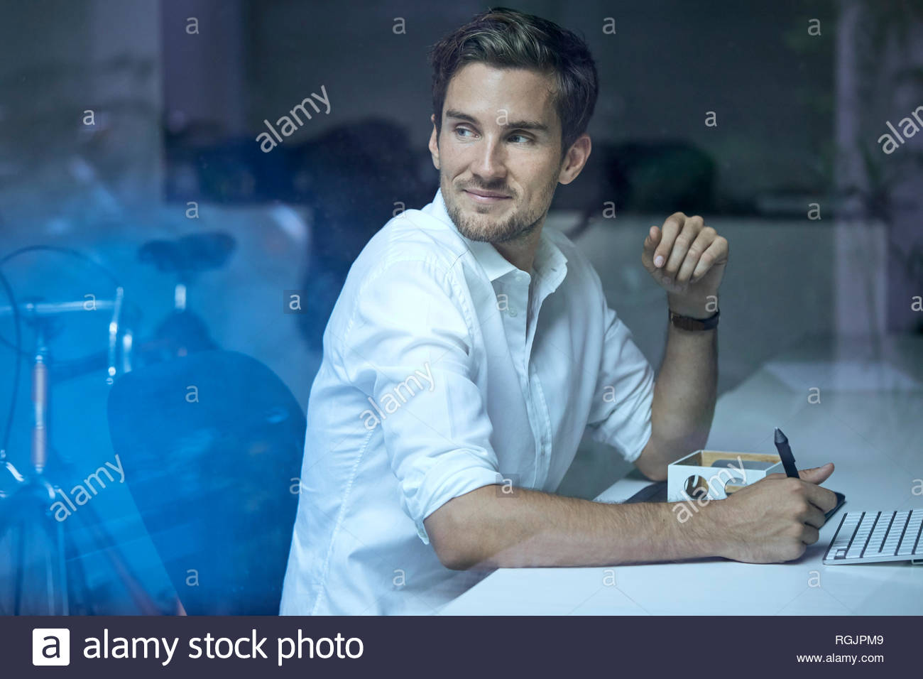 Portrait of content young man behind windowpane sitting at his desk watching something - Stock Image