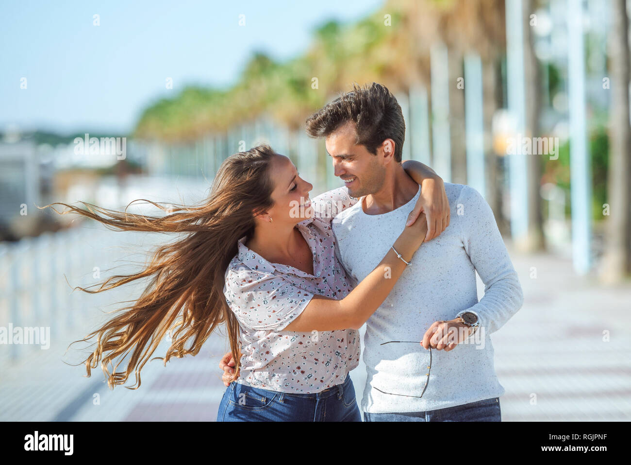 Happy young couple hugging on promenade Stock Photo