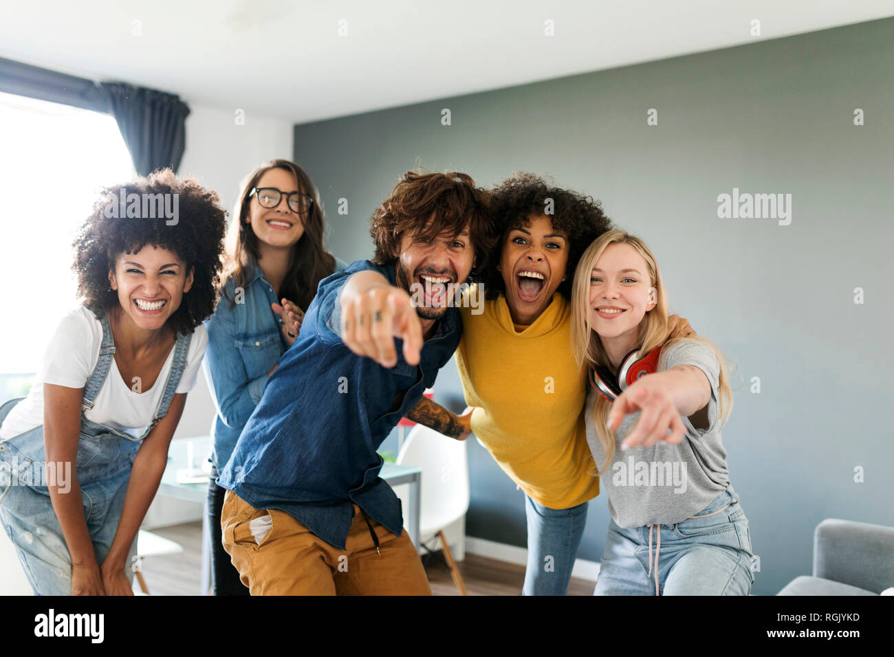 Portrait of cheerful friends at home with man and woman pointing finger - Stock Image