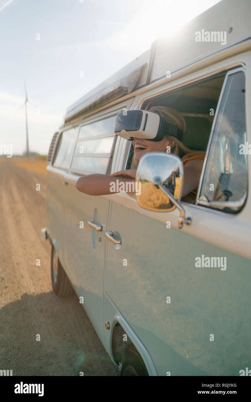 Happy woman wearing VR glasses leaning out of window of a camper van - Stock Image