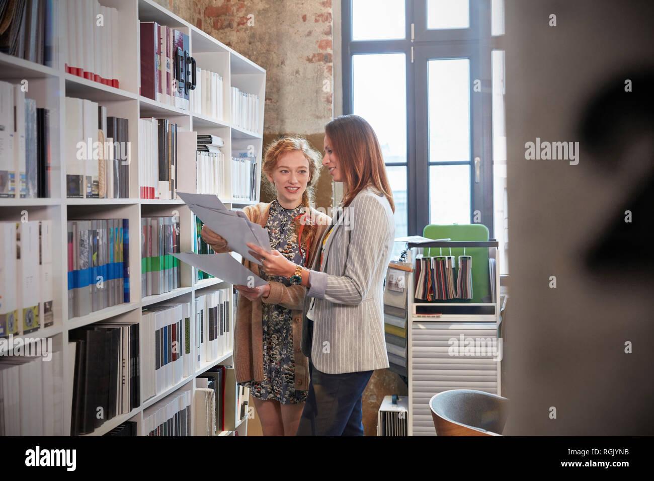 Two women choosing files in shelf in office - Stock Image