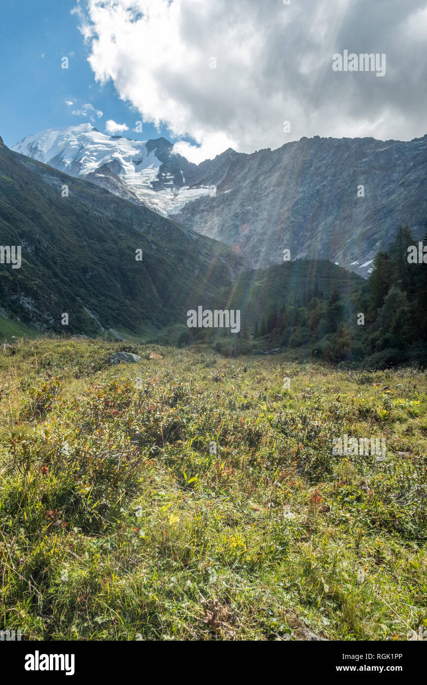 As a cloud moves over the Mont Blanc massif, sunbeams radiate colorful light down onto lush alpine meadows below Bionassay Glacier, France - Stock Image