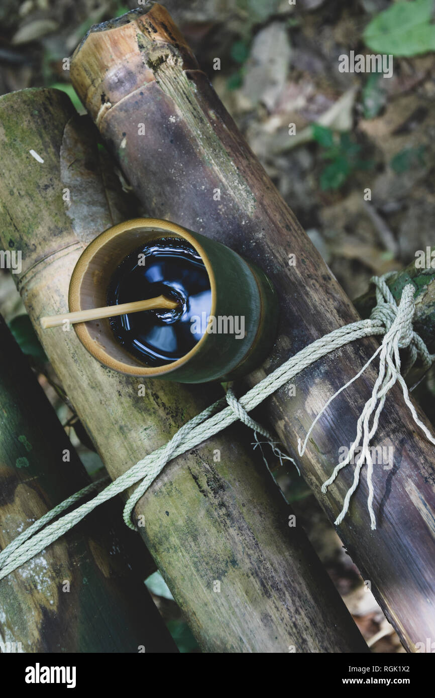 Fresh bio bamboo made cup and spoon filled with hot delicious hot coffee on a bench in the jungle in Thailand. Ecotourism - Stock Image