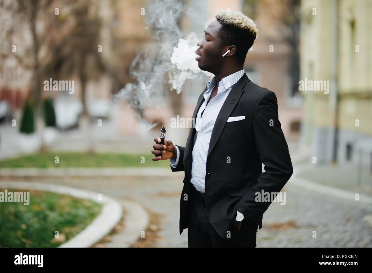 Handsome afro american business man with e-cigarette with smoke cloude standing on the city street - Stock Image