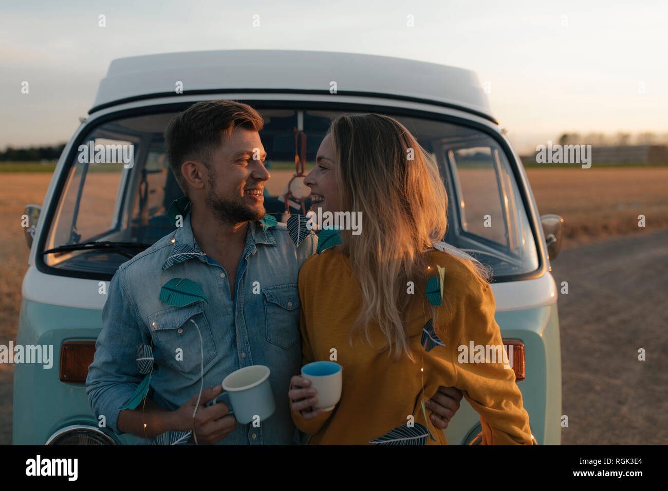 Happy young couple at camper van in rural landscape at sunset Stock Photo