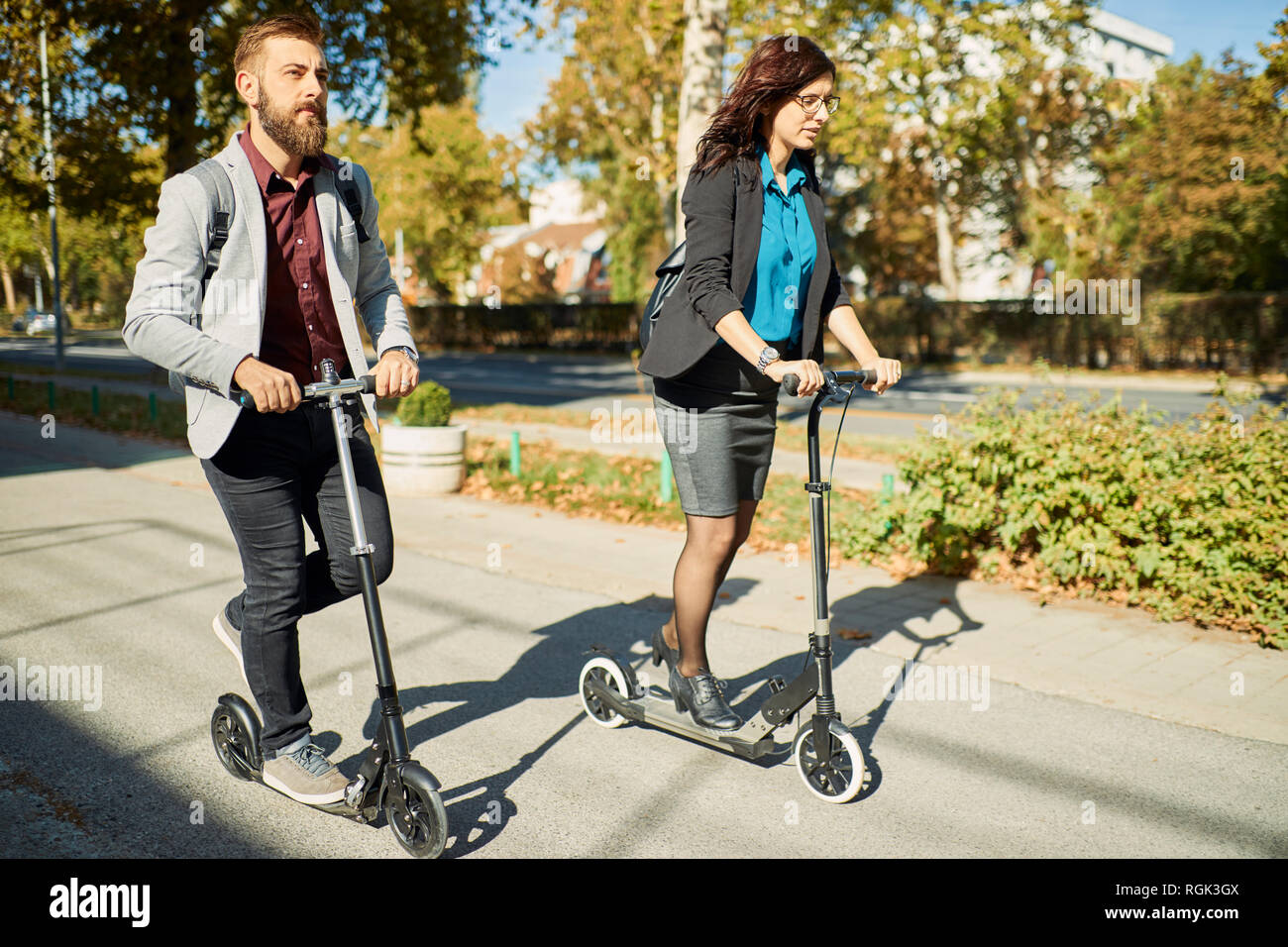 Businessman and businesswoman riding scooter Stock Photo