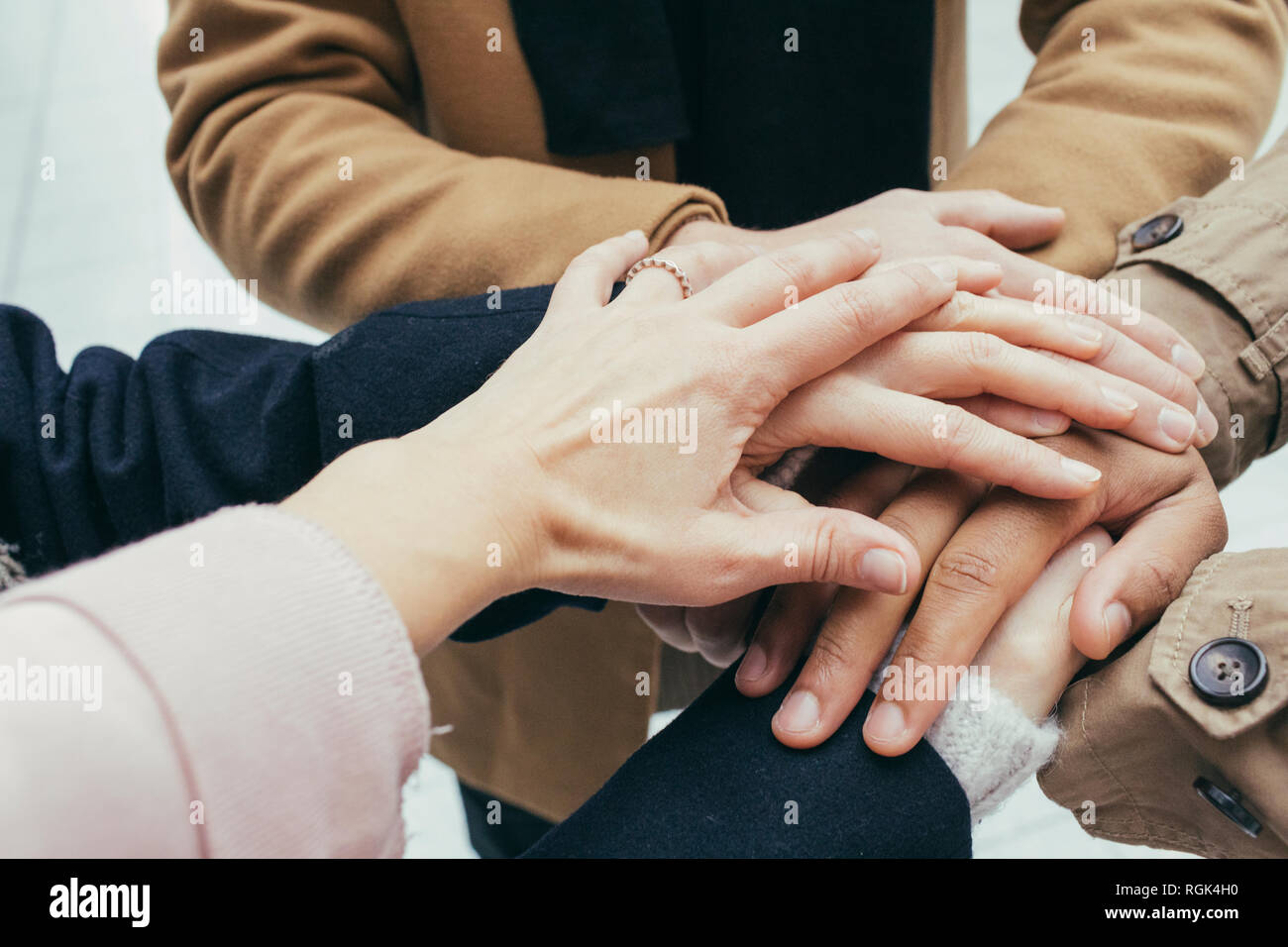 Group of friends putting hands together - Stock Image