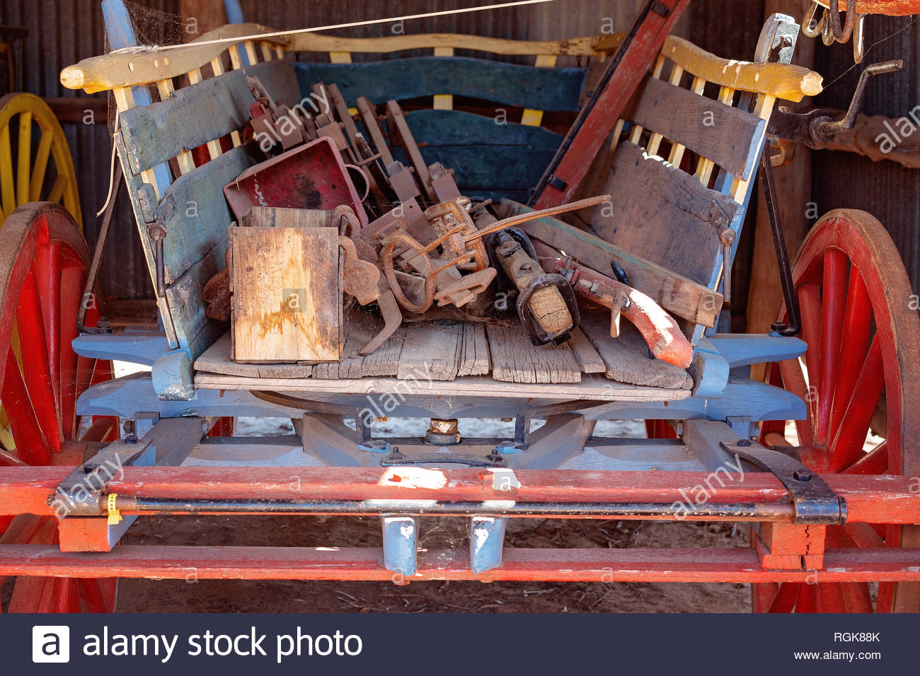 The back of an old vintage horse drawn wagon filled with ancient tools - Stock Image