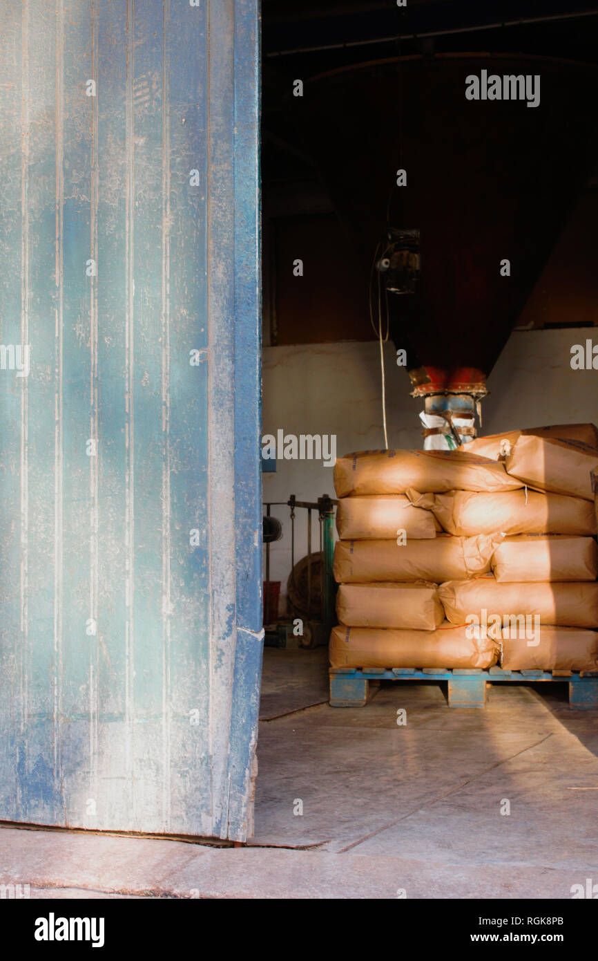 Open front door of the flour mill in Tournehem (France) with a pile of flour sacks indoors. - Stock Image