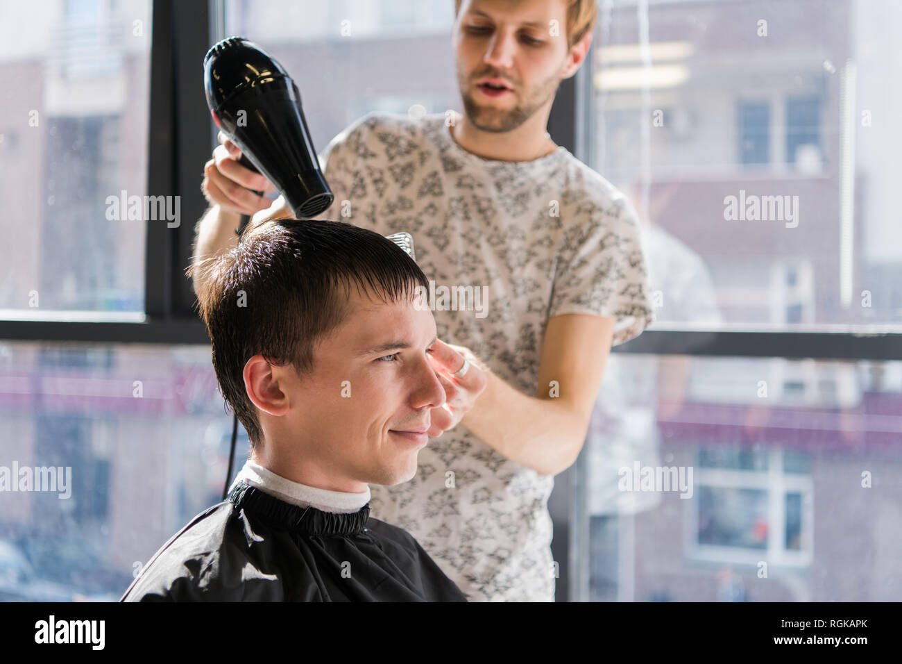 Drying, styling men's hair in a beauty salon - Stock Image