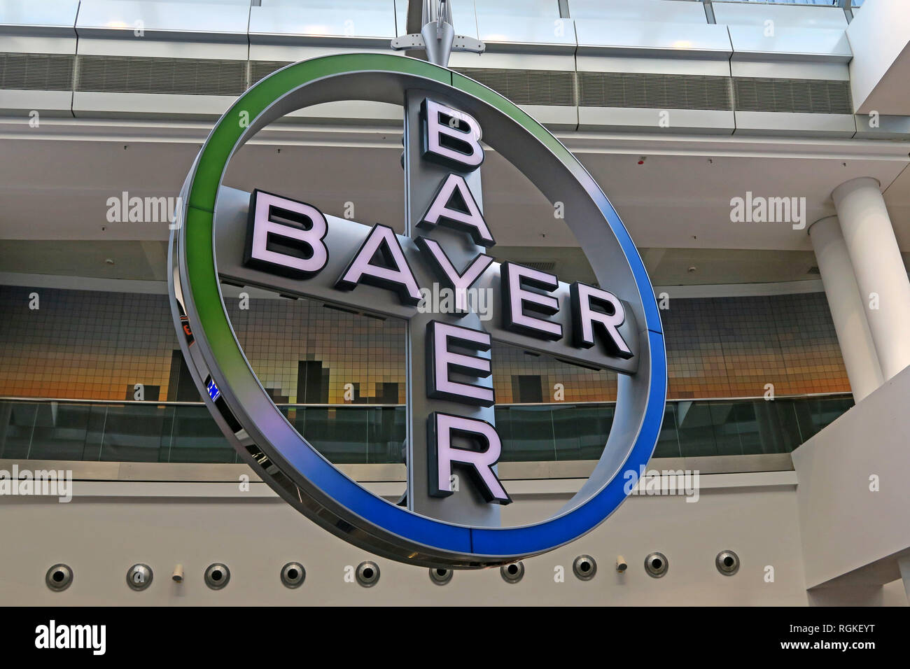 Bayer AG Cross Logo, rotating in Frankfurt Airport, Rhineland, Germany, Europe - Stock Image