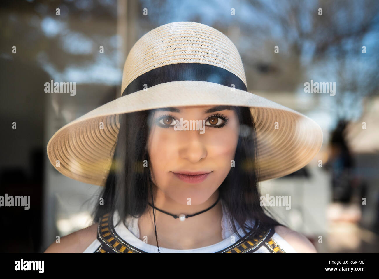 Beautiful young girl in hat looking through window - Stock Image