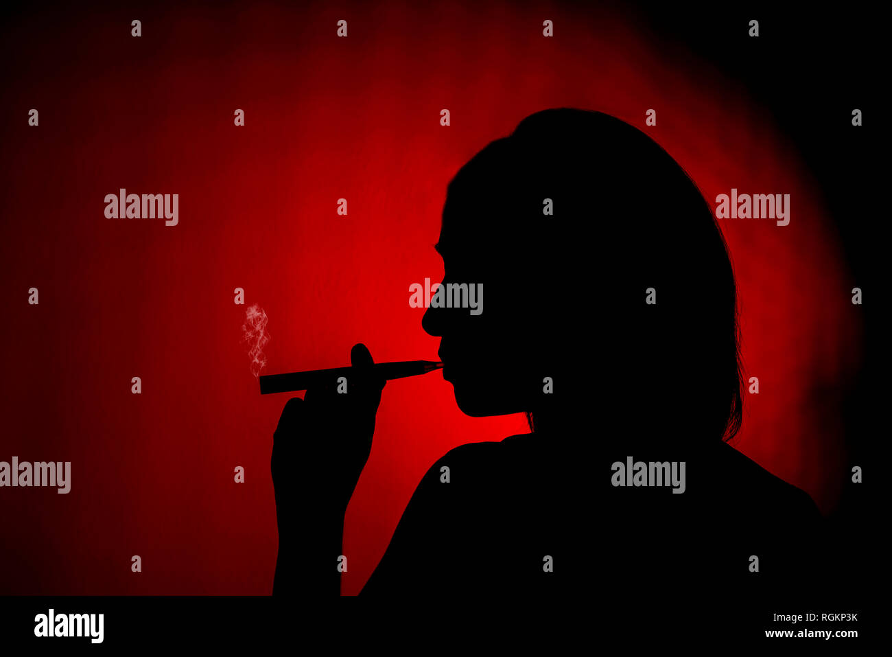 Silhouette of a female smoking an ecig on a red background - Stock Image
