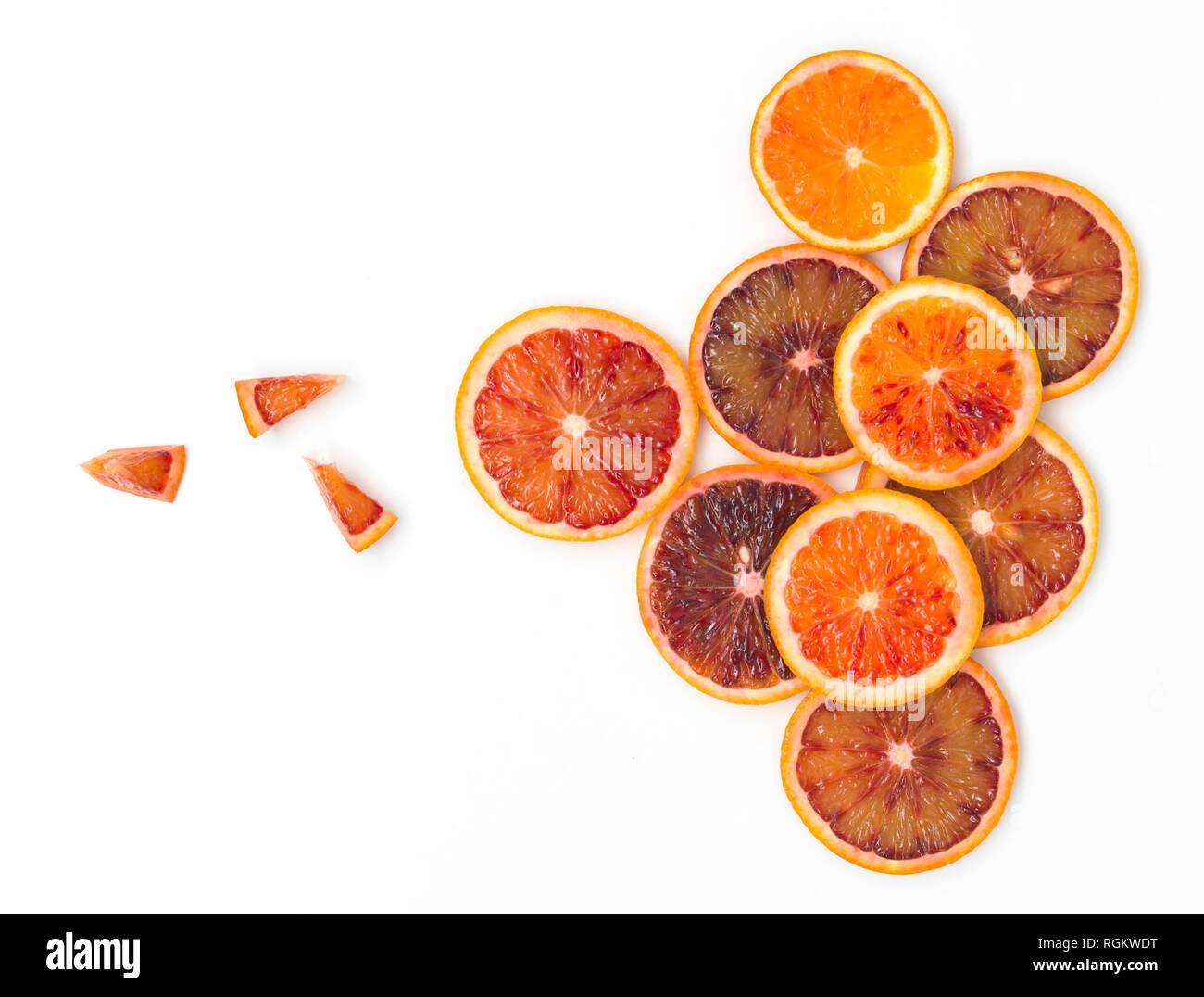 many fresh slices of blood oranges lie beautifully arranged on a white background - Stock Image