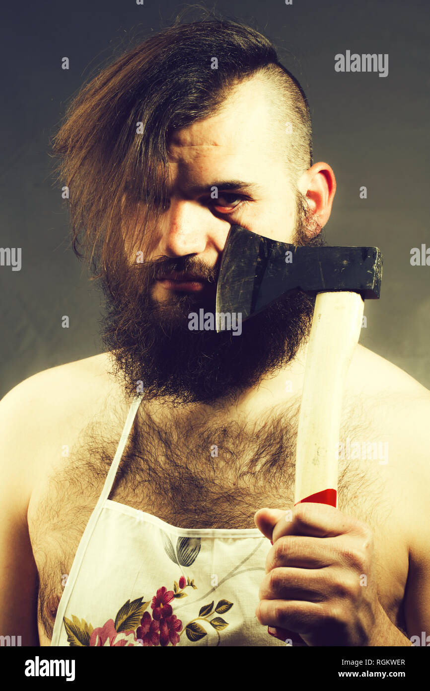 Man in housewife apron with axe - Stock Image