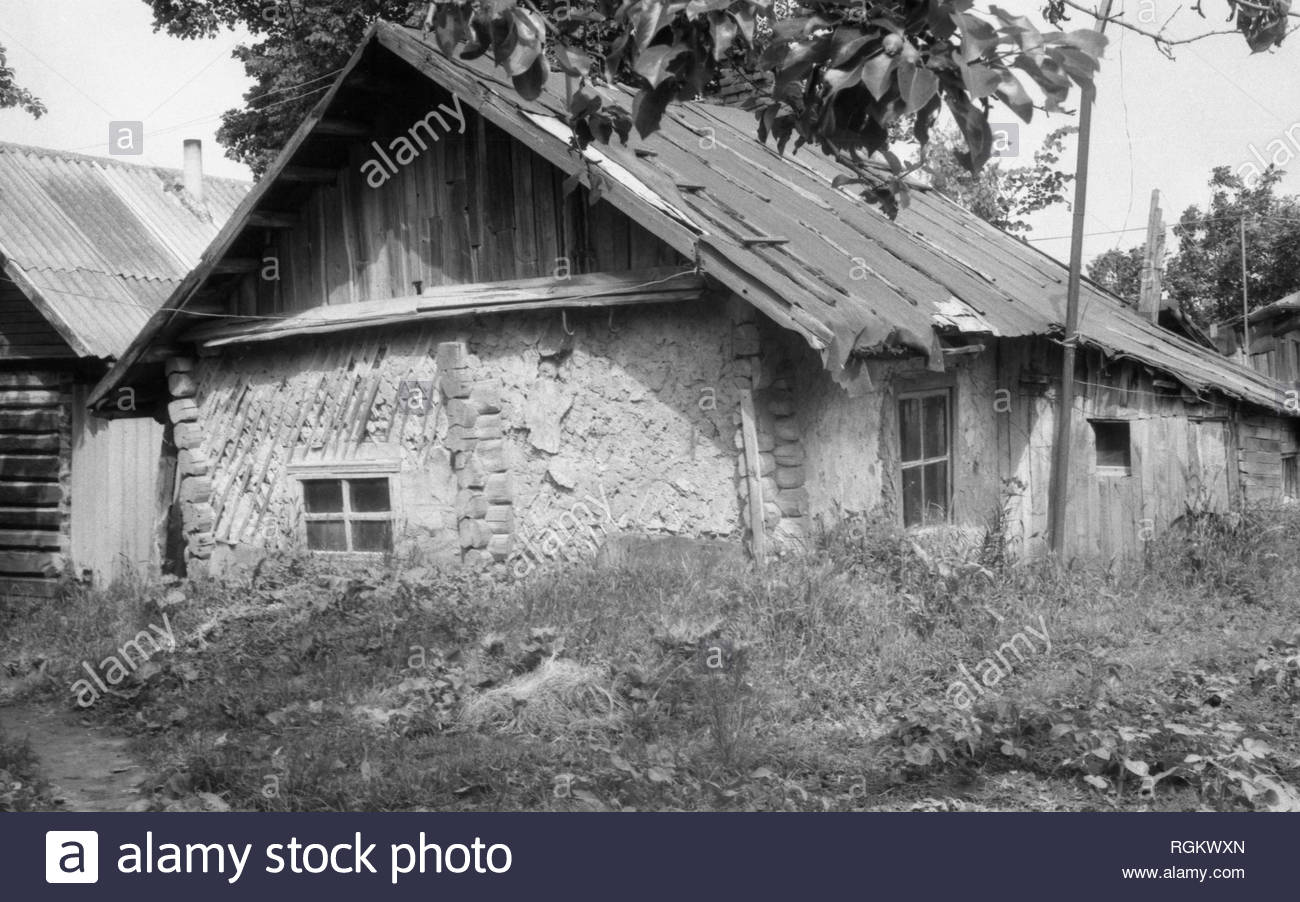 It's an old farmhouse. The walls of the house are faced with slats and covered with clay. The roof covered with roofing material, considerably was bent. But anyway an old woman lived in that house. She was my neighbour. The house was demolished long time ago. - Stock Image