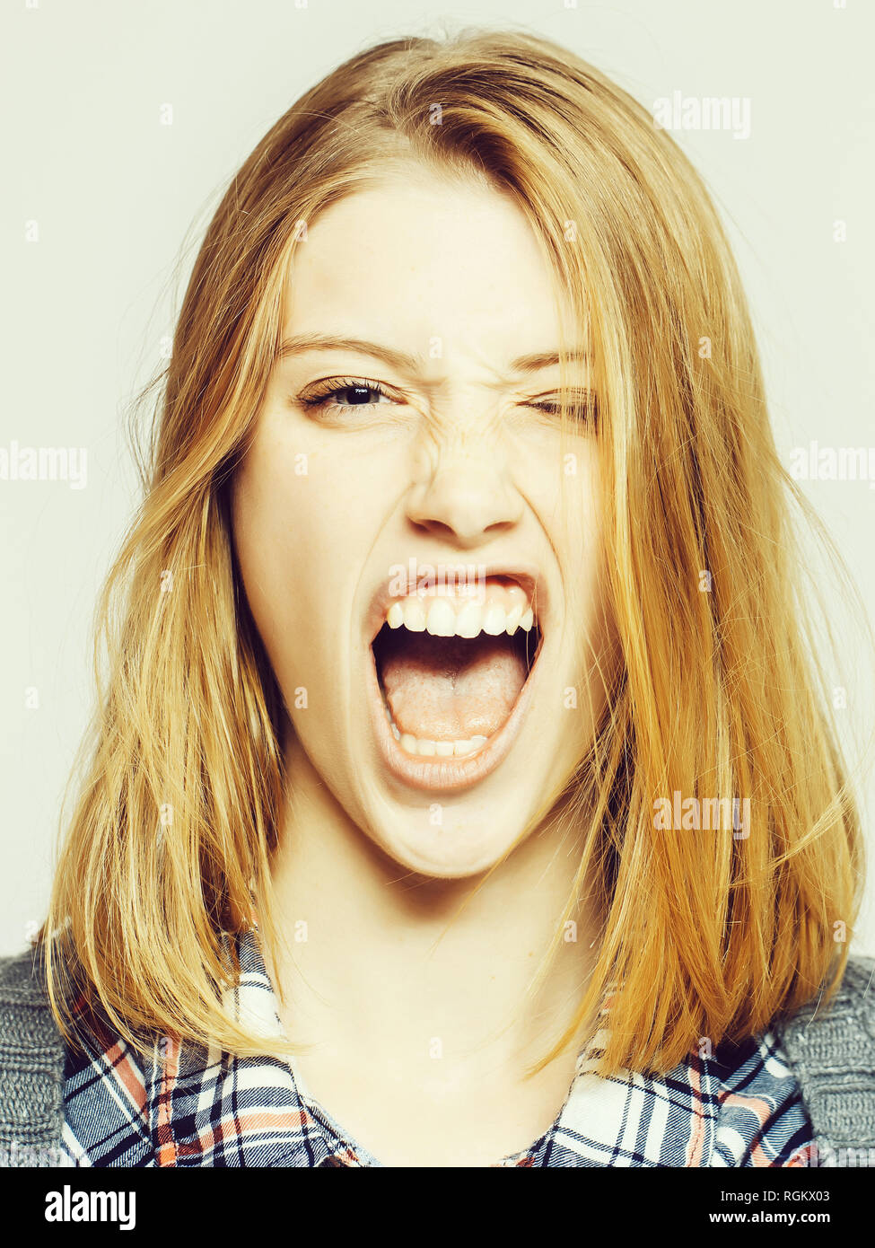 Angry pretty girl grimaces - Stock Image