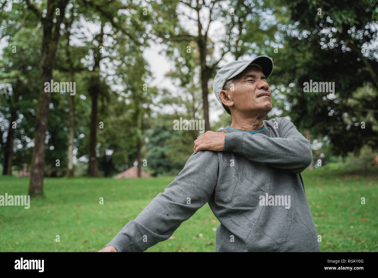 senior male asian having sore shoulder and pain on his joints  - Stock Image