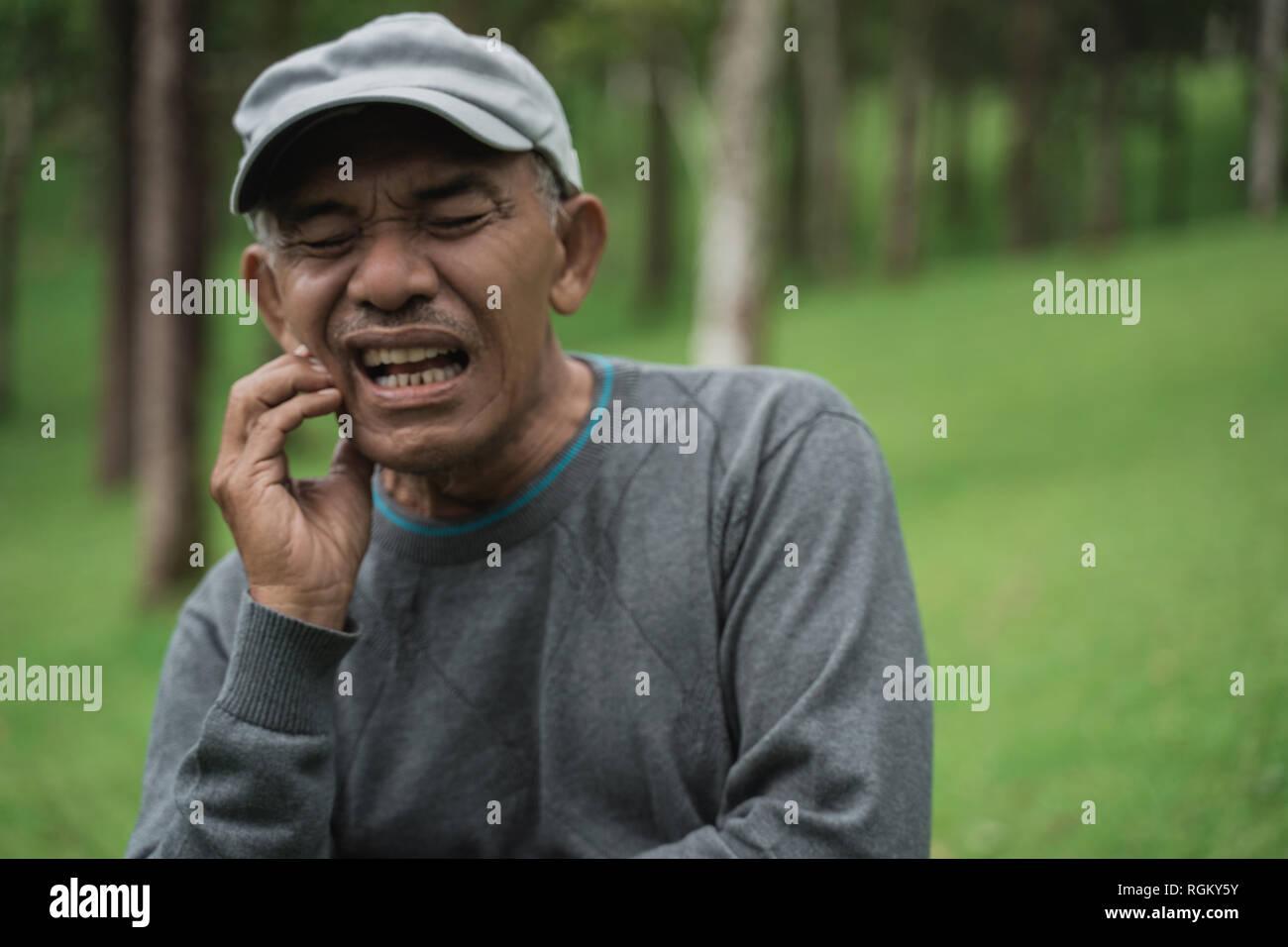 senior asian male having toothache - Stock Image