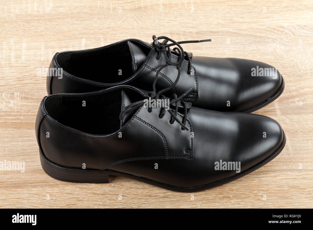 Close up picture of mens footwear Black leather elegant shoes on wooden background Stock Photo