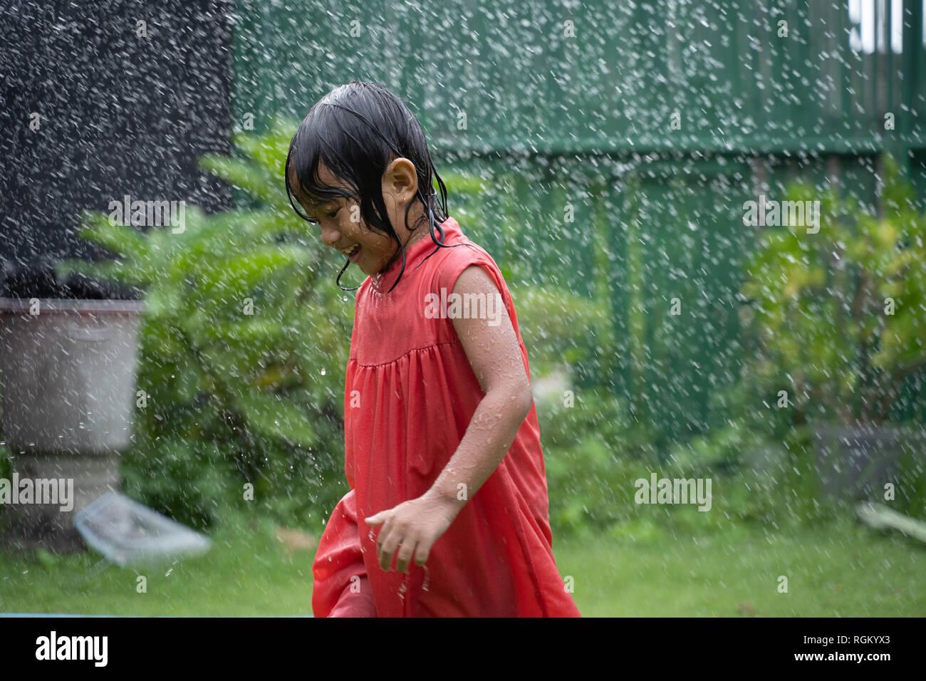 kid enjoying playing with water splash in garden - Stock Image