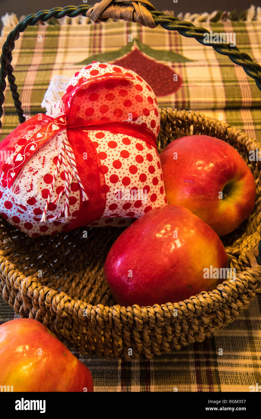 Apples in a basket on a kitchen table. - Stock Image