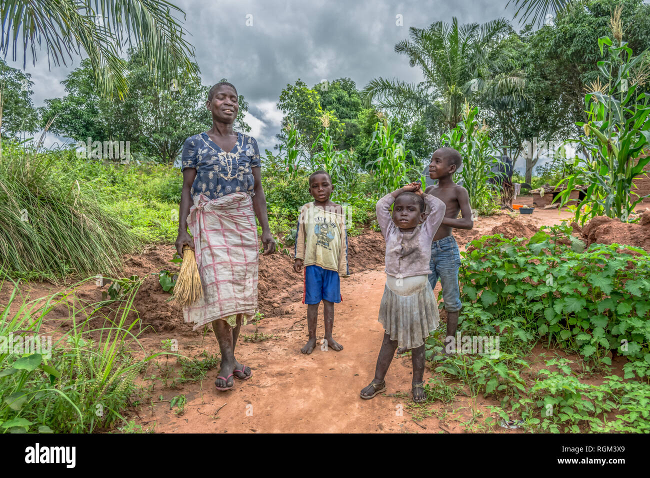 Malange / Angola - 12 08 2018 : View of an Angolan family, mother with her three children, in front of her small farmland - Stock Image