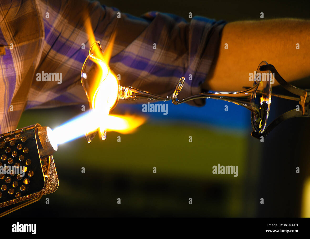 close up of glass blower making fancy glass vase with flaming torch - Stock Image