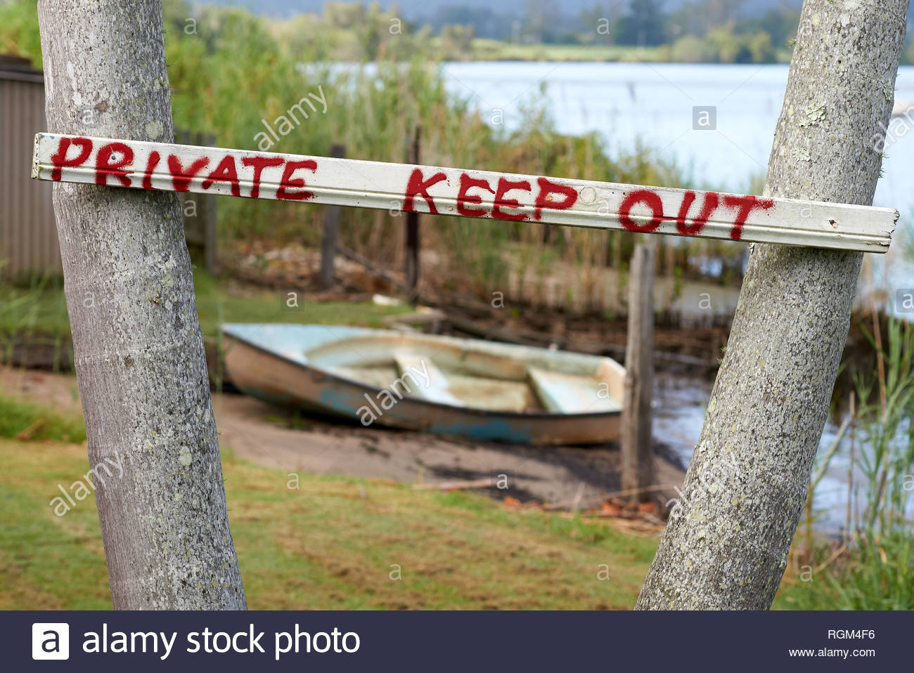A homemade 'private keep out' sign - red painted letters on white - nailed between two palm trunks, with a beached wooden dinghy and a river behind. - Stock Image