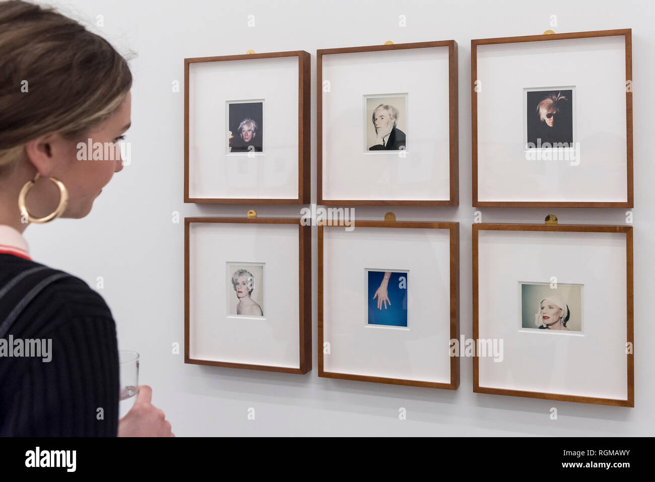 London, UK.  30 January 2019. A staff member views a series of self-portraits (1977 to 1986) by Andy Warhol. Preview of 'Andy Warhol Polaroid Pictures', an exhibition of over 60 portrait and self-portrait Polaroid photographs by Andy Warhol.  The works, which depict artists, actors, politicians and friends of his Factory entourage in New York during the 1970s and 80s, are on display 2 February to 13 April 2019 at Bastian Gallery in Mayfair.  Credit: Stephen Chung / Alamy Live News - Stock Image