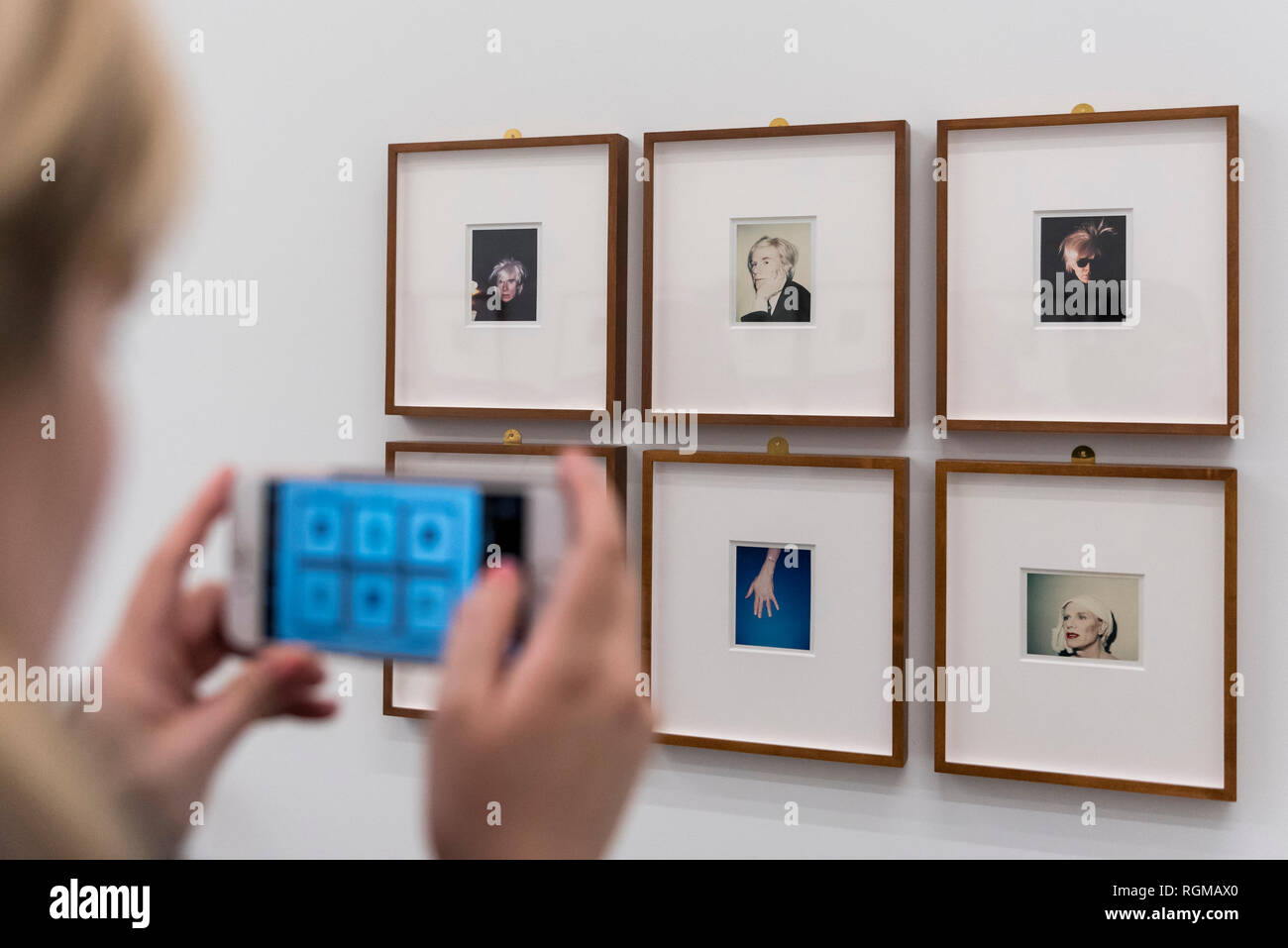 London, UK.  30 January 2019. A visitor photographs a series of self-portraits (1977 to 1986) by Andy Warhol. Preview of 'Andy Warhol Polaroid Pictures', an exhibition of over 60 portrait and self-portrait Polaroid photographs by Andy Warhol.  The works, which depict artists, actors, politicians and friends of his Factory entourage in New York during the 1970s and 80s, are on display 2 February to 13 April 2019 at Bastian Gallery in Mayfair.  Credit: Stephen Chung / Alamy Live News - Stock Image
