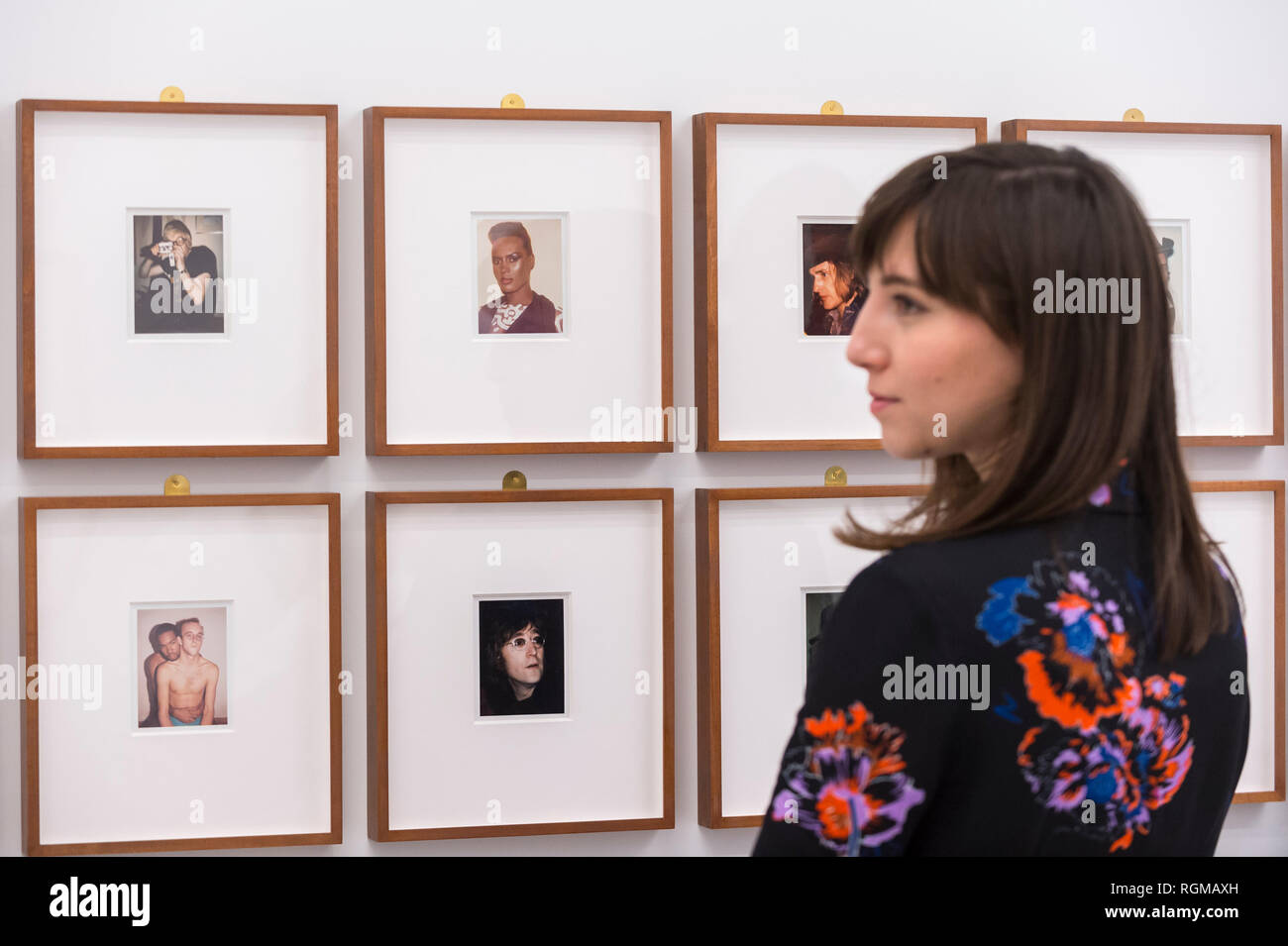 London, UK.  30 January 2019. A staff member views a series of portraits by Andy Warhol, including 'David Hockney' (1972), 'Grace Jones' (1974), 'Dennis Hopper' (1972), 'Keith Haring and Juan Dubose' (1983) and John Lennon (1971). Preview of 'Andy Warhol Polaroid Pictures', an exhibition of over 60 portrait and self-portrait Polaroid photographs by Andy Warhol.  The works, which depict artists, actors, politicians and friends of his Factory entourage in New York during the 1970s and 80s, are on display 2 February to 13 April 2019 at Bastian Gallery in Mayfair.  Credit: Stephen Chung / Alamy Li - Stock Image