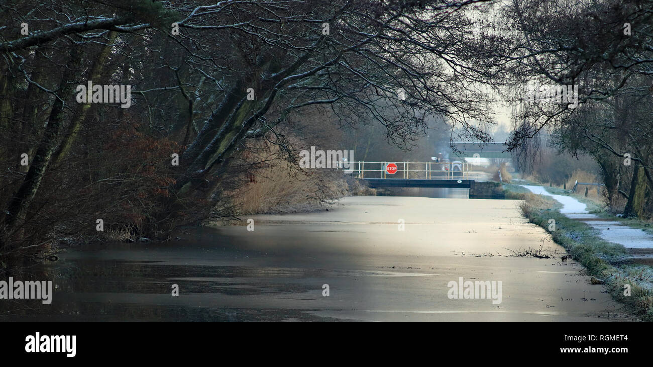 Rufford, Lancashire. 30th January 2019. A light covering of snow fell over West Lancashire over night into 30.1.19. The Rufford branch of the Leeds and Liverpool can also froze over a bit at the back of Rufford Old Hall, the view towards Town Meadow swing bridge as the sun is coming up. Credit: Colin Wareing/Alamy Live News - Stock Image