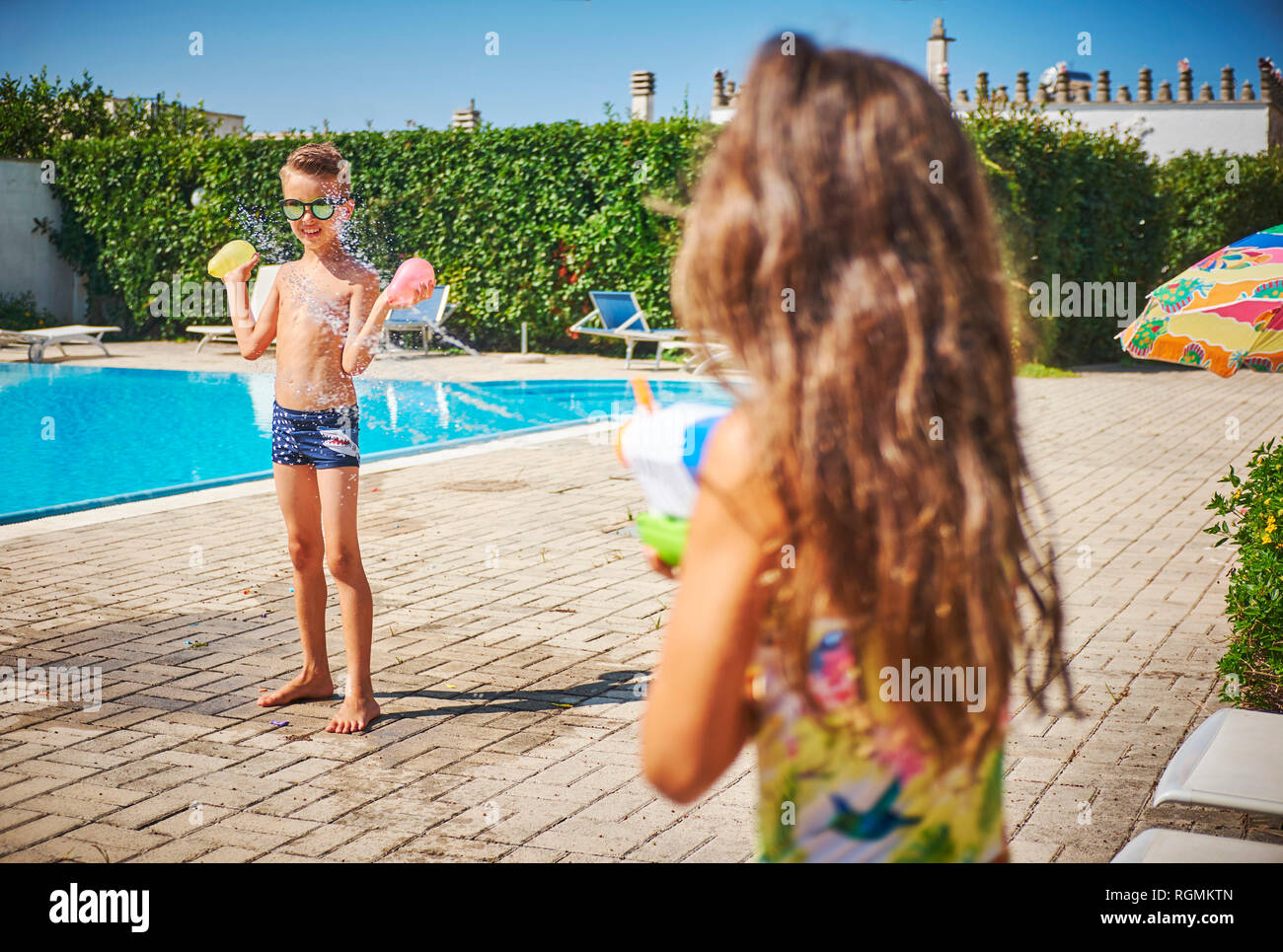 Girl with water gun splashing at boy holding water bombs at the poolside - Stock Image