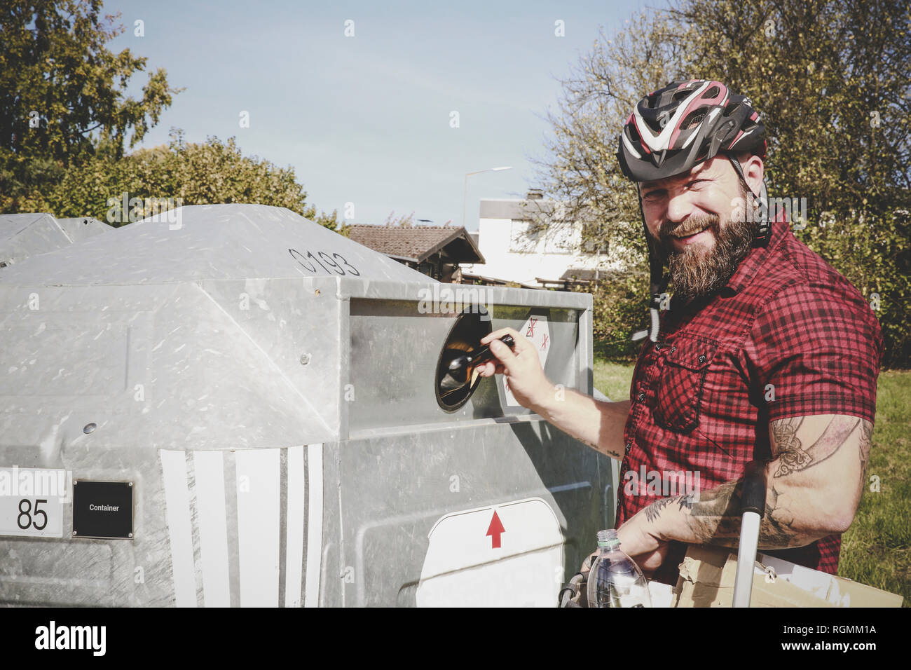 Portrait of man recycling glass bottle in bottle bank - Stock Image