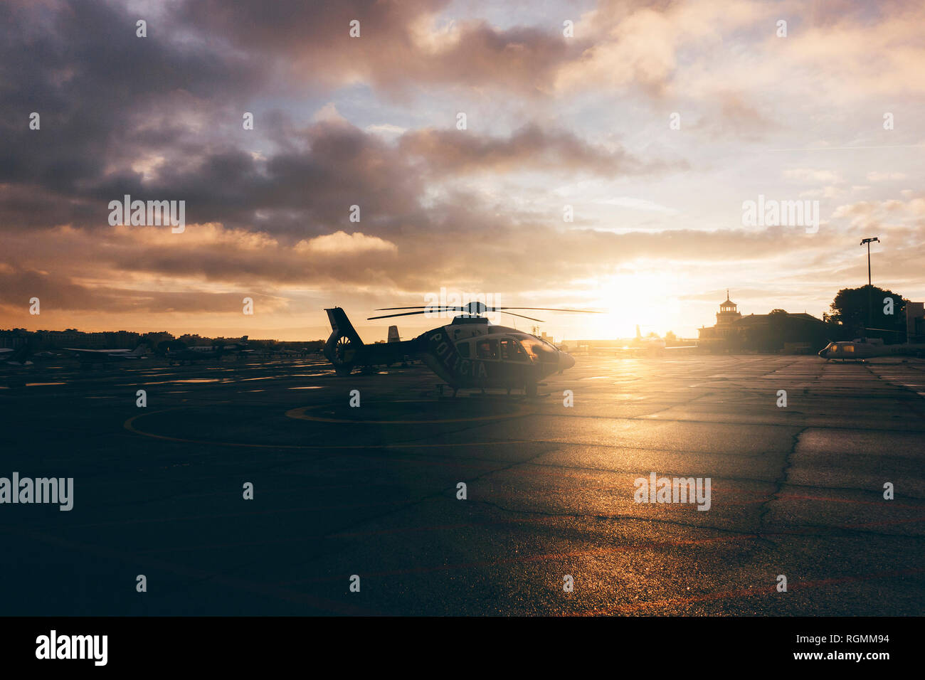 Helicopter on landing place during sunset Stock Photo