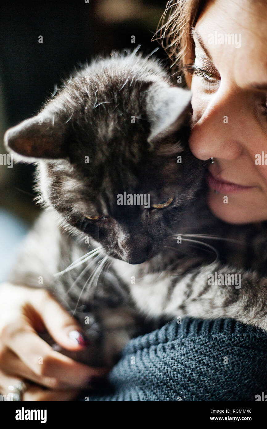 Woman hugging her grey tabby cat Stock Photo
