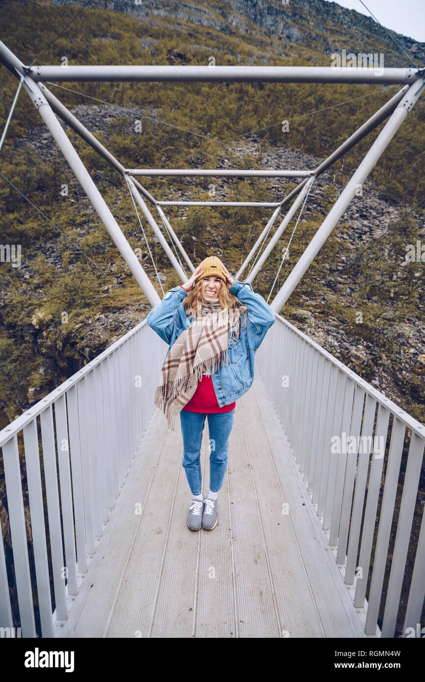 Young woman standing on a windy bridge, holding her cap - Stock Image