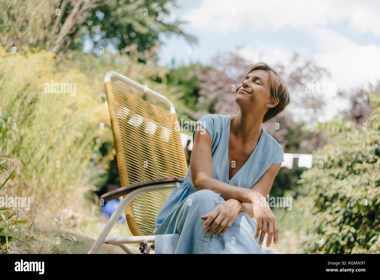Relaxed woman sitting in garden on chair with closed eyes Stock Photo