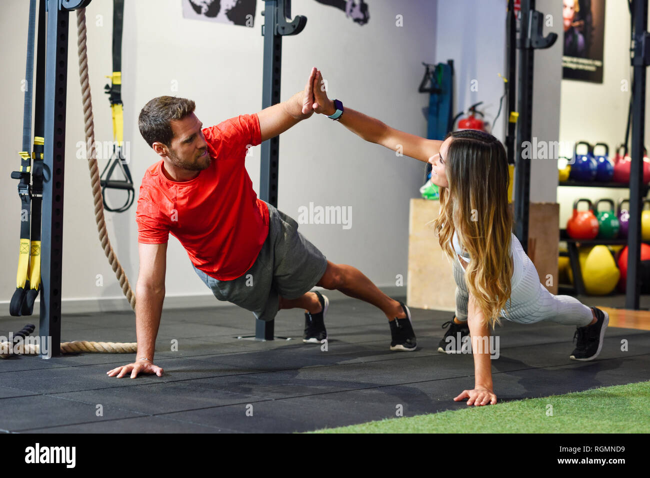 Couple exercising side plank with high-five in a gym - Stock Image
