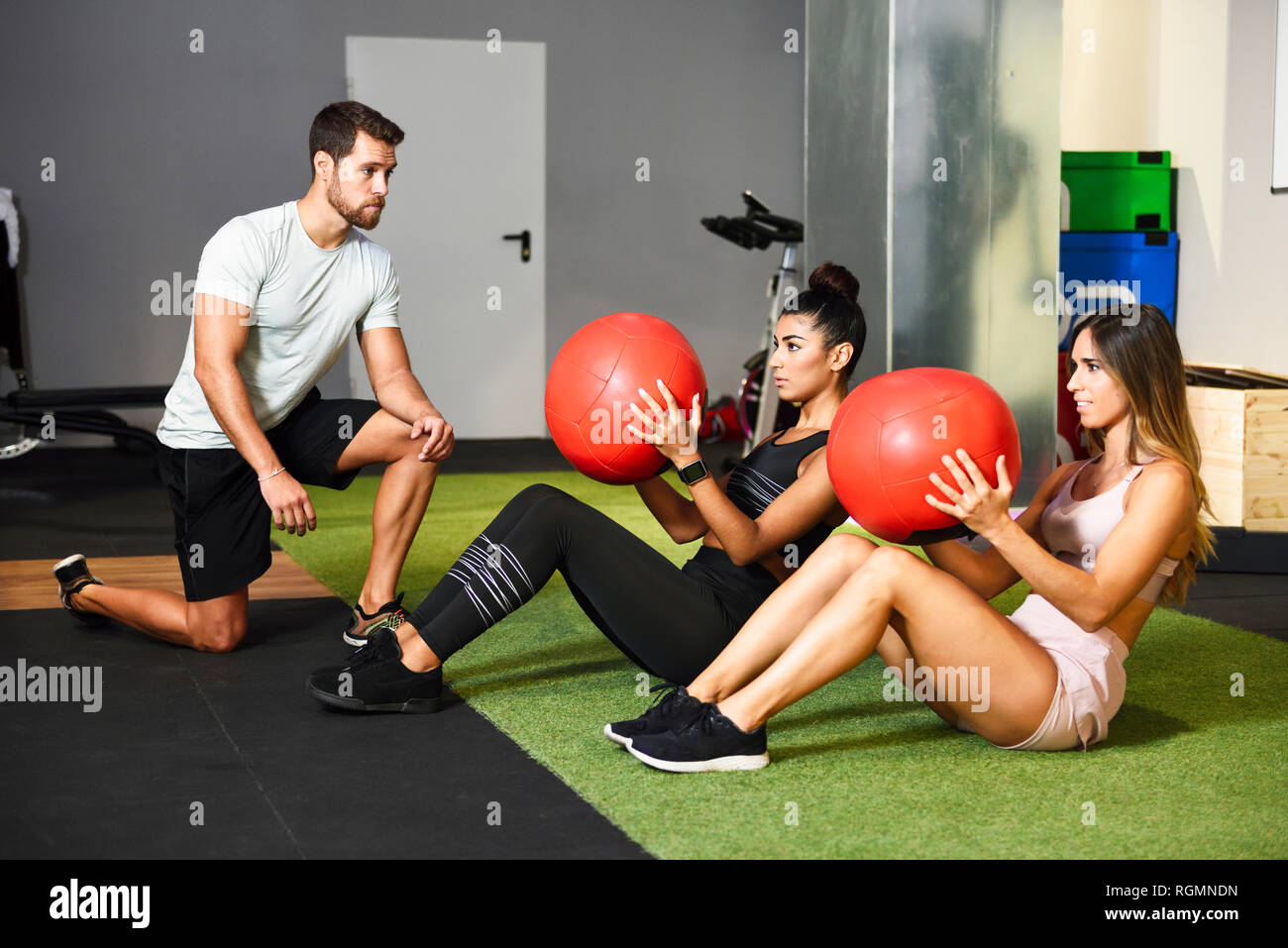 Young people doing ab training with fitness balls - Stock Image