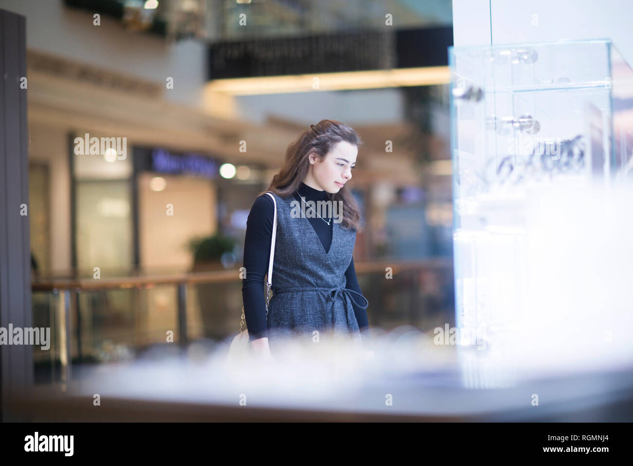 Young woman looking at showcase in a shopping mall - Stock Image