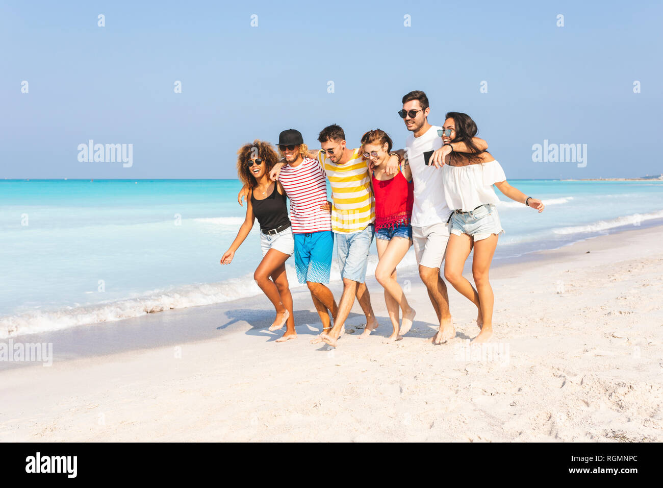 Group of friends walking on the beach - Stock Image