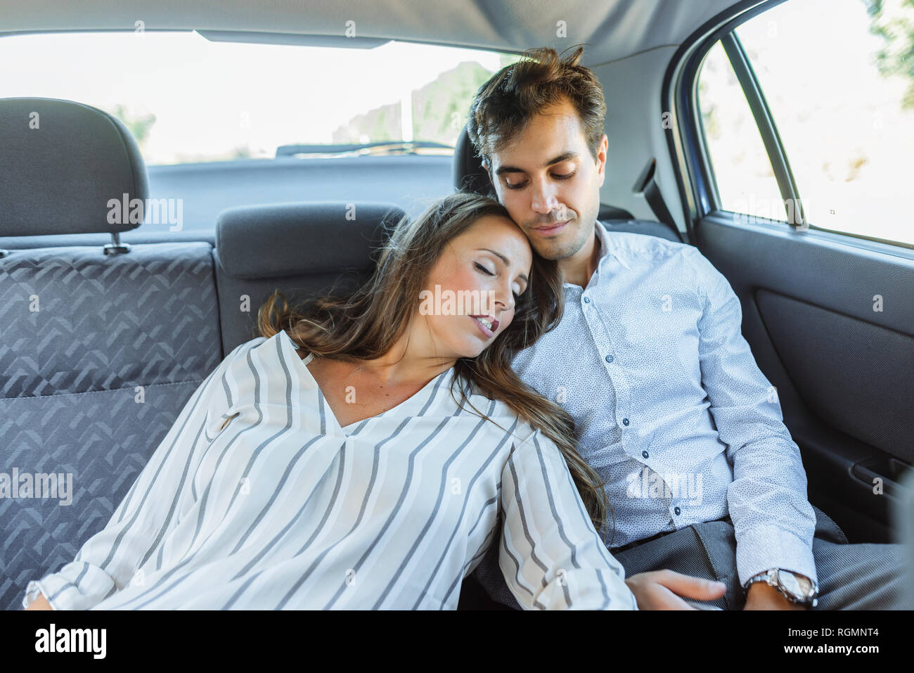 Woman sleeping on back seat of a car leaning against man - Stock Image