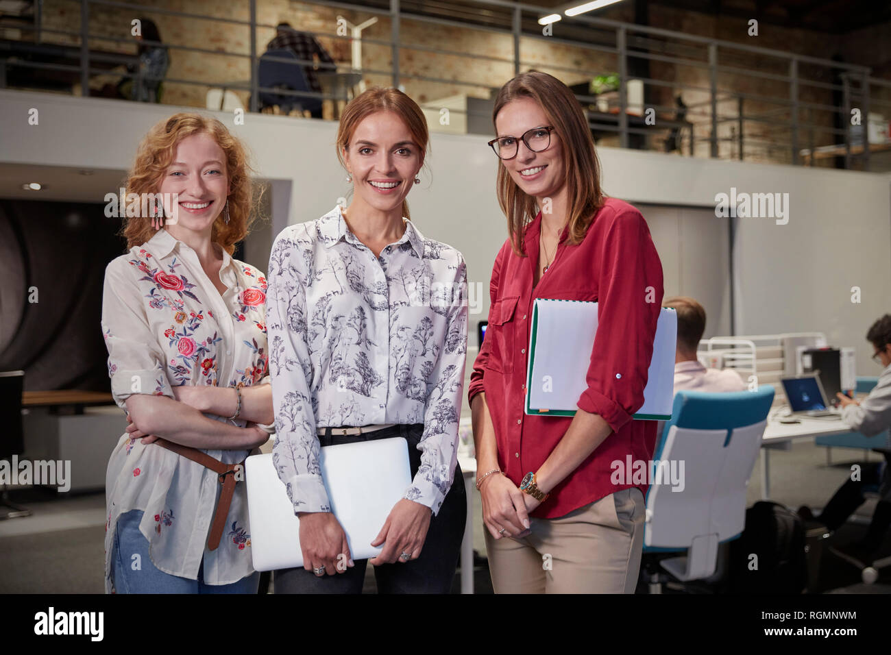 Group portraits of female colleagues in office, holding files - Stock Image