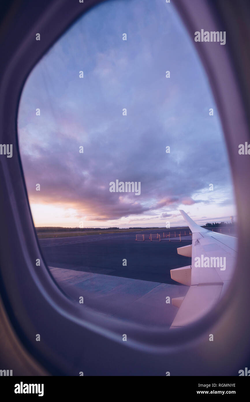 View of airplane wing through window at twilight Stock Photo