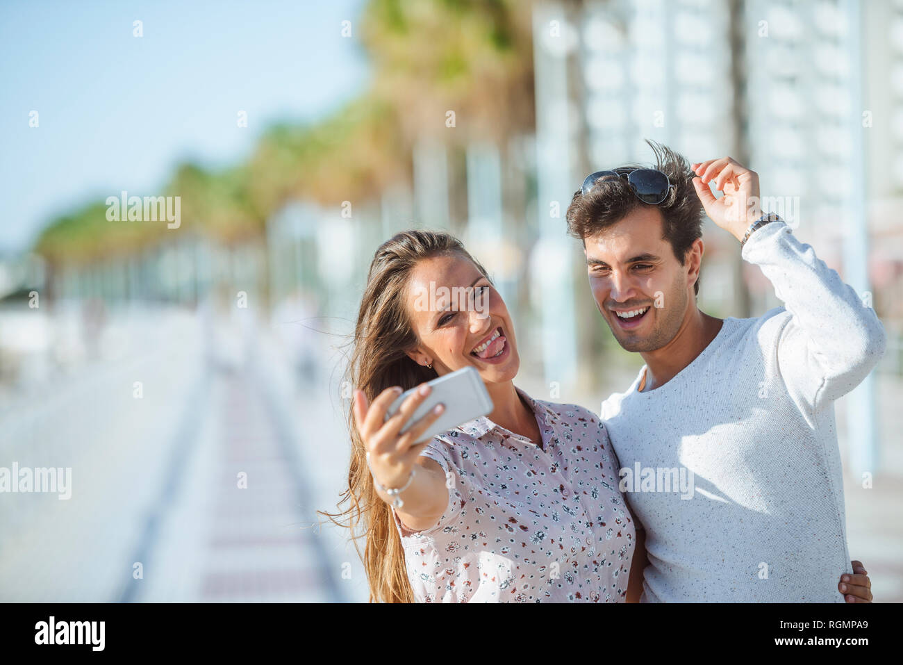 Happy young couple taking a selfie on promenade - Stock Image