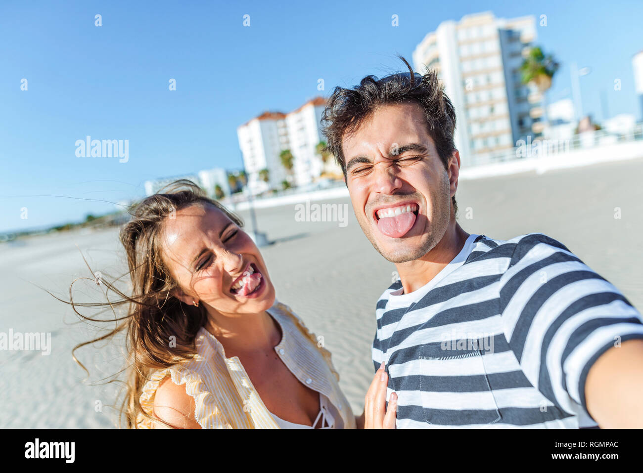Funny selfie of a happy young couple on the beach - Stock Image