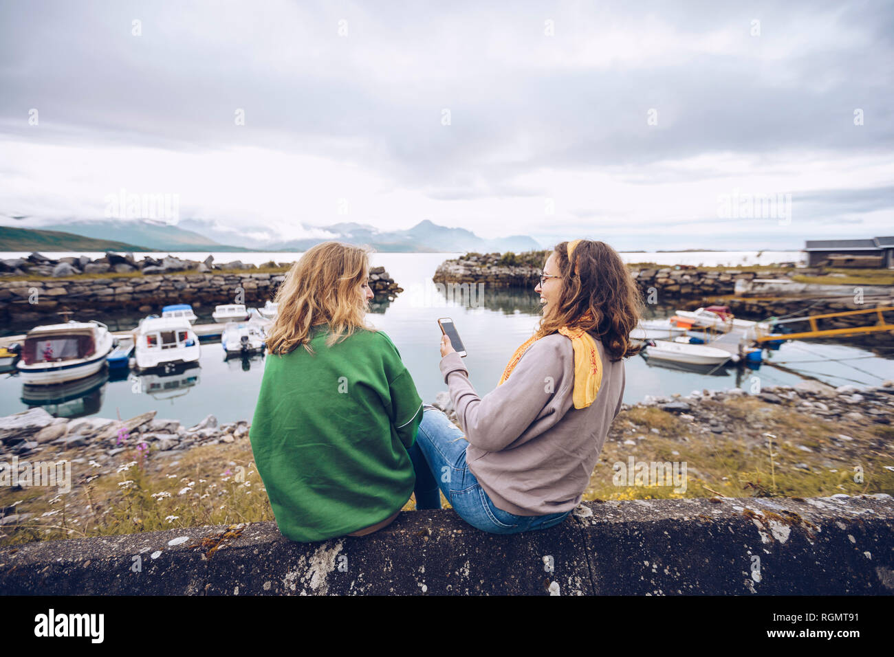 Norway, Senja, two young woman sitting at a small harbor with cell phone Stock Photo