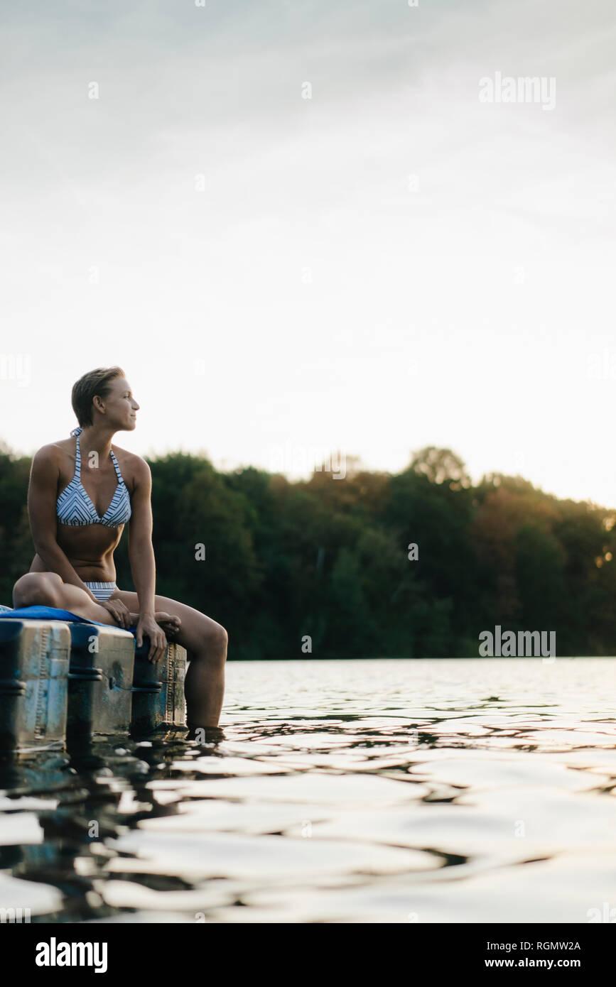 Woman wearing a bikini sitting on a float at a lake Stock Photo